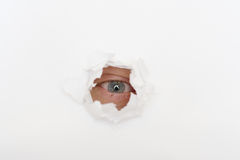Eye in the hole of white paper. Squinted eye of eavesdropper in the hole of white paper Royalty Free Stock Photography
