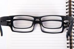 Eye i vetri vetri dell'occhio con il libro sui precedenti Immagine Stock