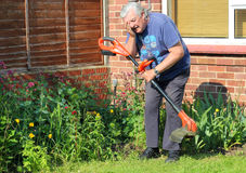 Eye injury, no protection. An elderly man strimming the lawn and recieving an eye injury. Not wearing protection over his eyes has caused a flying stone to royalty free stock photos