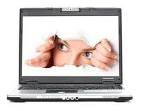 Eye la mirada a través del agujero en la pantalla de la computadora portátil Imagenes de archivo