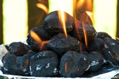 Eye level Flaming BBQ briquettes stock image