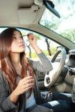 Eye-liner de port de jeune femme dans la voiture Photo libre de droits