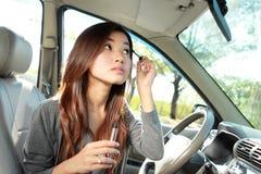 Eye-liner de port de jeune femme dans la voiture Photos stock