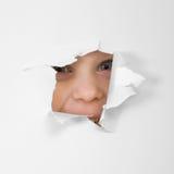 Eye lo sguardo attraverso il foro in foglio di carta Immagine Stock