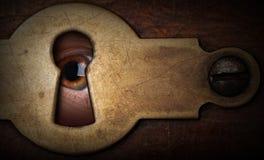 Eye lo sguardo attraverso un buco della serratura del metallo dell'annata Fotografia Stock Libera da Diritti