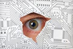 Eye lo sguardo attraverso un foro in circuito elettronico Fotografia Stock Libera da Diritti