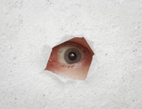Eye looking through hole in gray wall Stock Photos