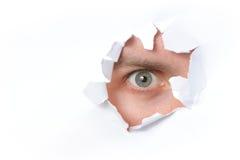 Eye looking through a hole in paper. Eye looking through a hole in a paper Royalty Free Stock Image