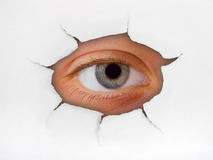 Eye looking through hole on paper Royalty Free Stock Photo