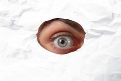 Eye looking through a hole in a paper. Eye looking through a hole in white paper Stock Photo