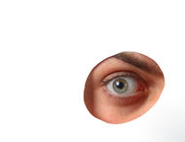 Eye looking through a hole in a paper. Eye looking through a hole in white paper Stock Photos