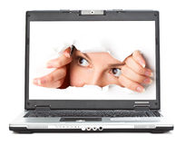 Eye looking through hole in screen of laptop Stock Images