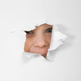 Eye looking through hole in sheet of paper Stock Image