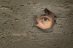 Eye looking through a hole in wall. Royalty Free Stock Photography