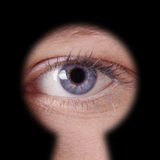Eye looking through keyhole. Close-up of human female blue eye looking through keyhole Stock Image