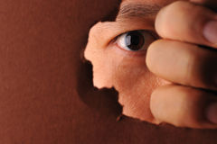 Eye looking through a paper hole Royalty Free Stock Image