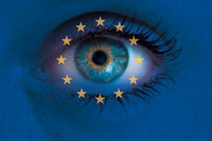 Eye looks through Europe flag background concept macro Royalty Free Stock Images