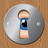 Eye looks through keyhole � peeping Royalty Free Stock Photo