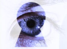 Eye looks through a keyhole Royalty Free Stock Photography