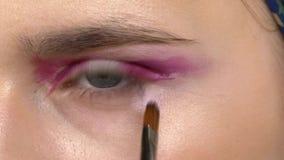 Eye make-up woman applying eyeshadow, making. Eye make up woman applying eyeshadow, making exotic, using a special brush, close up stock video