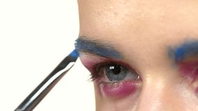 Eye make-up woman applying eyeshadow, making. Eye make up woman applying eyeshadow, making exotic, using a special brush, one eye, blue eyebrow, close up, on stock footage