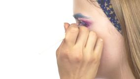 Eye make-up woman applying eyeshadow, making. Eye make up woman applying eyeshadow, making exotic, using a special brush, one eye, blue eyebrow, laterally, close stock footage