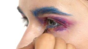 Eye make-up woman applying eyeshadow, making. Eye make up woman applying eyeshadow, making exotic, using a special brush, one eye, blue eyebrow, white blusher stock video footage