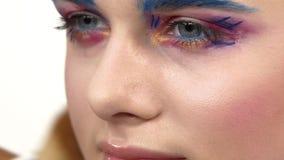 Eye make-up woman applying eyeshadow, making. Eye make up woman applying eyeshadow, making exotic, using a special brush, one eye, blue eyebrow, white blusher stock video