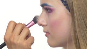 Eye make-up woman applying eyeshadow, making. Eye make up woman applying eyeshadow, making exotic, using a special brush, one eye, blue eyebrow, white blusher stock footage