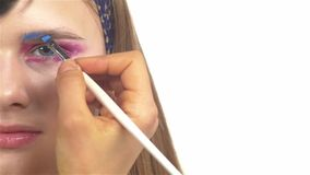 Eye make-up woman applying eyeshadow, making. Eye make up woman applying eyeshadow, making exotic, using a special brush, one part of face, blue eyebrow, close stock video footage