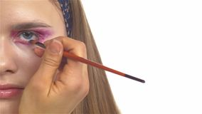 Eye make-up woman applying eyeshadow, making. Eye make up woman applying eyeshadow, making exotic, using a special brush, two eyes, blue eyebrow, close up, on stock footage