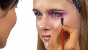 Eye make-up woman applying eyeshadow, making. Eye make up woman applying eyeshadow, making exotic, using a special brush, two eyes, blue eyebrow, close up, on stock video