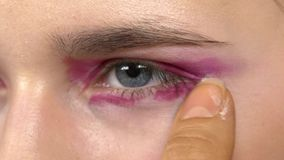 Eye make-up woman applying eyeshadow, making. Eye make up woman applying eyeshadow, making exotic, using a special brush, two eyes, close up stock video footage