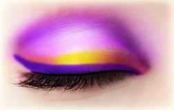 Eye makeup. Image of purple eye makeup, one closed eyeball with beautiful violet and golden eyeshadow Stock Images