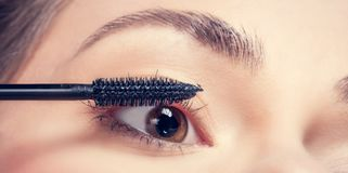Young woman applying mascara to her lashes. Eye makeup application. Close-up shot of a young woman applying mascara to her lashes Royalty Free Stock Images