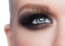 Eye makeup. Closeup of beautiful woman blue eye with bright stylish makeup with long lashes Stock Photos