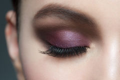 Eye makeup. Closeup of beautiful woman eye with bright violet stylish makeup with long lashes Royalty Free Stock Photography