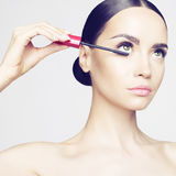 Eye makeup. Studio fashion photo of beautiful young lady applied mascara.  Beauty and care. Extension eyelashes. Spa salon. Perfect face makeup Stock Photography