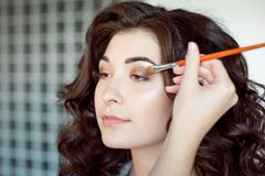 Eye makeup woman applying eyeshadow powder. Make up artist doing professional make up of young woman Stock Photos
