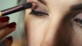 Eye makeup woman applying eyeshadow powder. Perfect nude makeup