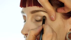 Eye makeup woman applying eyeshadow powder. Stylist is doing make up for female by eyeliner stock video