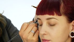 Eye makeup woman applying eyeshadow powder. Stylist is doing make up for female by eyeliner stock video footage