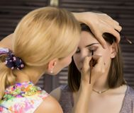 Eye makeup woman applying eyeshadow powder. Stylist is doing make up for female by eyeliner Royalty Free Stock Photography