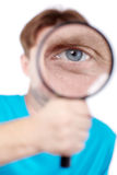 Eye of man, looking through magnifying glass Royalty Free Stock Image