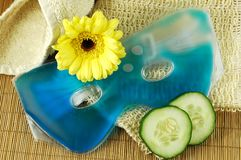 Eye Mask. Soothing blue eye mask with cucumber slices, towel, natural fiber cloth, and yellow daisy on a bamboo mat Royalty Free Stock Images