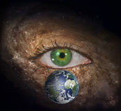 Eye in midst of Galaxy with Earth. Eye in midst of Galaxy and Earth  Some elements provided courtesy of NASA Royalty Free Stock Photo