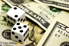 Eye on the money. Dice on cash with focus on presidents eye stock photography
