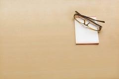 Eye a nota do vidro e a de papel na tabela de madeira Fotografia de Stock Royalty Free