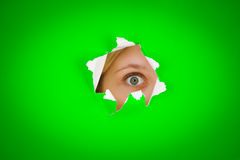 Eye peeping. Closeup of persons eye peeping through tear/hole in green background Stock Image