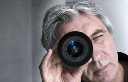 Eye of the photographer. Grey-haired senior looking through a lens Royalty Free Stock Photos